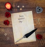 Vintage Valentine`s Day card with red roses, wooden decorations, red candle and ink and quill on vintage oak - top view royalty free stock photo