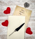 Vintage Valentine`s Day card in withe book with red cuddle hearts ink and quill - top view royalty free stock photos