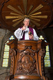 Antique pulpit and priest. Mature priest preaching in a beautiful antique 17th century wooden pulpit Stock Photo