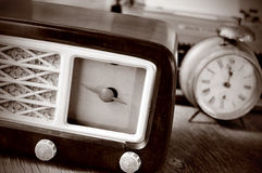 Antique radio, alarm clock and typewriter, in sepia toning. An antique radio receptor and some other antiques, such an alarm clock and a typewriter in the Stock Image