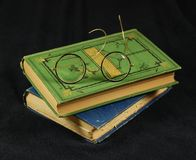 Antique reading glasses and old books. Antique wire framed reading glasses sit folded on stacked old books Royalty Free Stock Photography