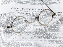 Antique reading glasses on page of bible Stock Images