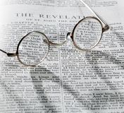 Antique reading glasses on page of bible Royalty Free Stock Images