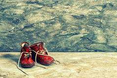 Antique red baby shoes. Vintage Instagram style Stock Photos