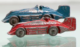 Antique red and blue toy race cars. Two antique toy race cars from the 1920's, lined up with the focus on one red racer. Each race car has a driver and are Royalty Free Stock Photography
