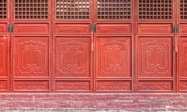 The antique red Chinese wooden carved doors of temple Stock Photos