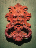 Antique red door knocker of an old door in Italy. Royalty Free Stock Image
