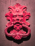 Antique red door knocker of an old door in Italy. Royalty Free Stock Photography