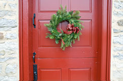 Antique red door with wreath. A view of a red, antique Dutch door with a simple pine bough Christmas wreath Stock Photo