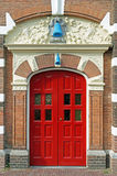Antique red double door. With two blue bells, in facade of a former factory built in the 17th century. Photo taken in Leiden, the Netherlands stock photography
