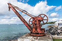 Antique red iron boat crane anchored in concrete along the shore. Line in urban town on St. Croix Royalty Free Stock Images