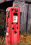 Antique red metal gas pump sits in the weather. Stock Image