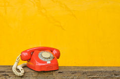 Antique red phone. On wood and yellow background Stock Images