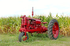 Antique Red Tractor and Corn. Antique red tractor in front of a corn field. Michigan, U.S.A.  12MP camera Stock Image