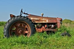 Antique Red Tractor Parked in Grass. An old red rusty tractor is parked and forgotten where it resides in the long grass and weeds Stock Photography