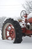 Antique Red Tractor in the Snow. Antique tractor half buried in the snow brings back old farm memories Royalty Free Stock Images