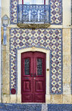 Antique red wooden door of a tiled house. Stock Image
