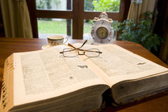Antique reference book. An antique reference book with eyeglasses and an old clock stock images