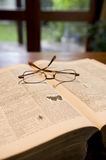 Antique reference book and glasses. An antique reference book with old yellow pages and a pair of glasses on top Royalty Free Stock Images