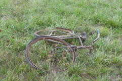 Antique or retro oxidized bicycle left down on the grass Royalty Free Stock Photos