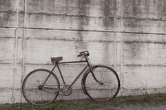 Antique or retro oxidized bicycle outside on a concrete wall Royalty Free Stock Image