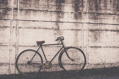 Antique or retro oxidized bicycle outside on a concrete wall Stock Photos