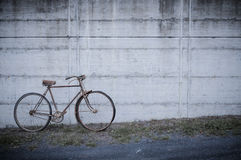 Antique or retro oxidized bicycle outside on a concrete wall Royalty Free Stock Images