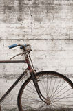 Antique or retro oxidized bicycle outside on a concrete wall Royalty Free Stock Photography