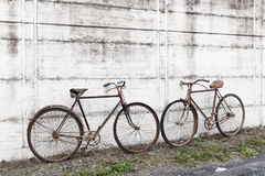 Antique or retro oxidized bicycle outside on a concrete wall Stock Photo