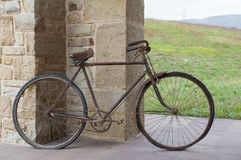 Antique or retro oxidized bicycle outside on a stone wall Royalty Free Stock Photos