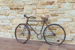 Antique or retro oxidized bicycle outside on a stone wall Stock Photo