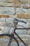 Antique or retro oxidized bicycle outside on a stone wall Stock Images