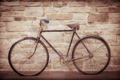 Antique or retro oxidized bicycle outside on a stone wall Royalty Free Stock Image