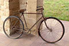 Antique or retro oxidized bicycle outside on a stone wall Stock Photos