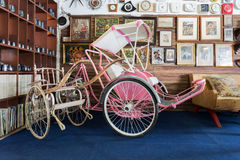 Antique rickshaw  and tricycle in the vintage warehouse gallery. Royalty Free Stock Images