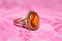 ANTIQUE RING. This delicate antique ring is made of rose gold and an orange gem. Inside the metal rim it is in-printed with the year 1918. It belonged to my Stock Photos