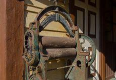 Antique rolling machine in front of house. Old equipment used to dry clothes by passing them between two rollers that press the. Water from the material vintage stock images