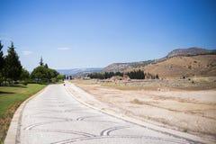 Antique Roman Hierapolis. Roman Hierapolis with adjacent remains of buildings,and modern road, Pamukkale, Turkey. UNESCO World Heritage Stock Image