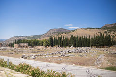 Antique Roman Hierapolis. Roman Hierapolis with adjacent remains of buildings,and modern road, Pamukkale, Turkey. UNESCO World Heritage Stock Photos