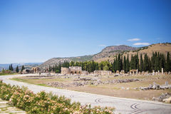Antique Roman Hierapolis. Roman Hierapolis with adjacent remains of buildings,and modern road, Pamukkale, Turkey. UNESCO World Heritage Stock Images