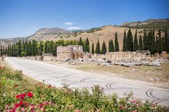 Antique Roman Hierapolis. Roman Hierapolis with adjacent remains of buildings,and modern road, Pamukkale, Turkey. UNESCO World Heritage Royalty Free Stock Photo