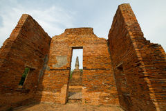 Antique ruined brick wall of temple in Thailand on blue sky back Stock Photos