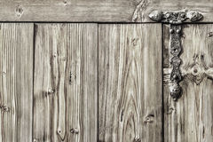 Antique Rustic Pine Wood Barn Door - Detail. Photograph of old, weathered, rustic, knotted Pine wooden door, with wrought iron hinges - detail Stock Image