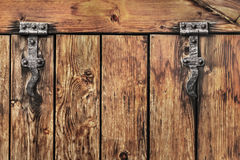 Antique Rustic Pine Wood Barn Door - Detail. Photograph of old, weathered, rustic, knotted Pine wooden door, with wrought iron hinges - detail Stock Photo