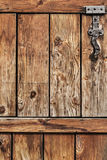 Antique Rustic Pine Wood Barn Door - Detail. Photograph of old, weathered rustic Pine wooden door, with wrought iron hinges - detail Stock Images