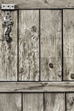 Antique Rustic Pine Wood Barn Door - Detail. Photograph of old, weathered rustic Pine wooden door, with wrought iron hinges - detail Stock Image