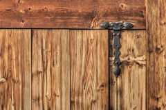 Antique Rustic Pine Wood Door With Wrought Iron Hinge - Detail. Photograph of old, weathered rustic Pine wooden door, with wrought iron hinges - detail Royalty Free Stock Image