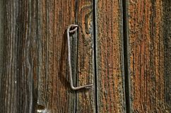 Antique rusty hook hangs on a door. A very weathered wood door covered with patina has a rusty hook hanging from a eye hook Royalty Free Stock Photo