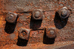 Antique Rusty Nuts on Industrial Rust Metal Bolts. Antique rusty metal square nuts locked with rust and corrosion on old heavy duty bolts holding a thick and Royalty Free Stock Image