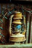 Antique rusty oil/petrol lamp with old christmas lights.  Royalty Free Stock Images